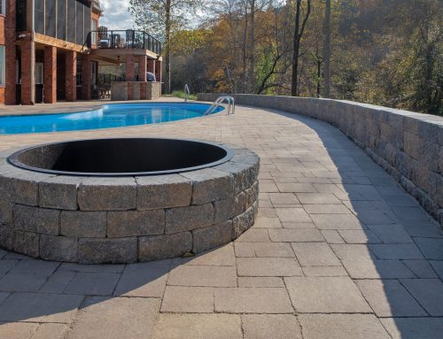 Hardscape poolside paradise featuring pavers throughout, a fire pit for chilly nights, and an extensive retaining wall